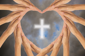 Hands make heart shape and Christian cross in the sky.