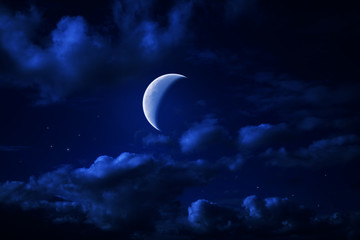 Night blue cloudy sky with stars and a moon