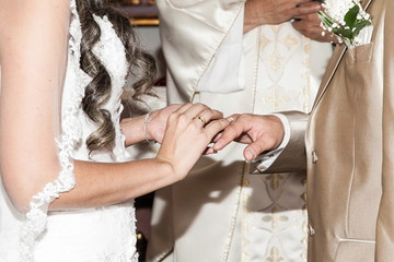 Bride putting a wedding ring on the finger of her groom during a wedding ceremony