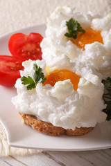 Beautiful toast with baked eggs Orsini on a plate close-up. vertical