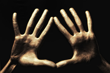 hands in gold paint on black background