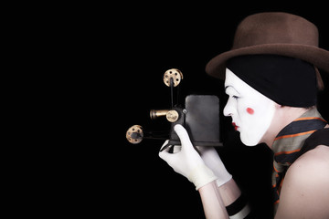 mime in white gloves and brown hat with camera