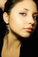 Portrait of a young beautiful girl with earrings