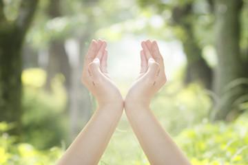 光を包み込むような手