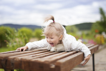 A little girl with delight lies on the bench