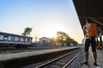 Backpacker with orange bag waiting a train at platform.
