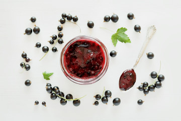 Blackcurrant jam in jar on white background, top view