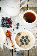 Porridge with blueberry and cup of tea on the vintage napkin on the white wooden background, Russian style spoon in desaturated tone, moody lighting