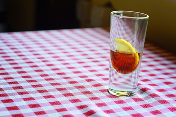 Short drink with lemon on red and white checkered background