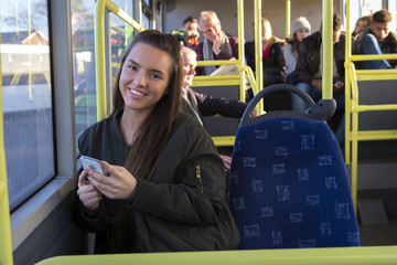 Young woman using her smartphone on the bus