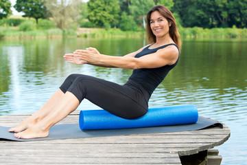 Sportliche Frau demonstriert Sit Up auf dem Foarmroller / Pilates