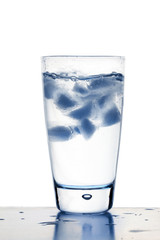 Blue tinted ice cubes in glass of water