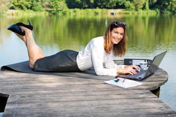 Attraktive Frau mit Arbeitsplatz am Teich - Home Office