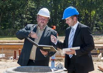 bauingenieur zeigt seinem kollegen wo er unterzeichnen soll