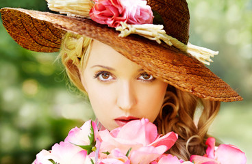 Beautiful girl with flowers in the garden with straw hat. Natural beauty.