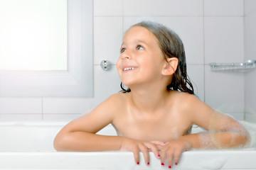 Adorable toddler girl relaxing in bathtub