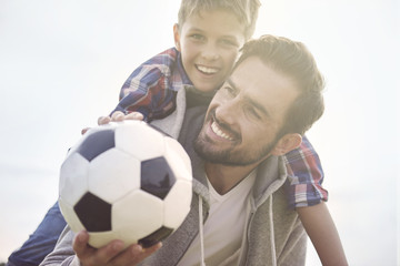 Father teaches son how to play football