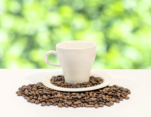 Cup of coffee with coffee beans, on white and green bokeh backgr