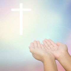open hands praying the cross on blur sky background.