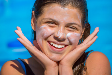 Protect sun cream applied to the face of smiling expressive young girl