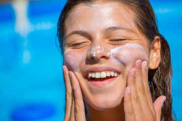 Protect sun cream applied to the face of smiling young girl