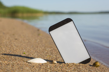 Smartphone sticking out of the sand on the beach