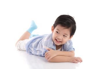 Cute asian boy lying on white background