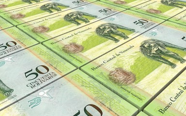 Venezuelan Bolivares bills stacks background.