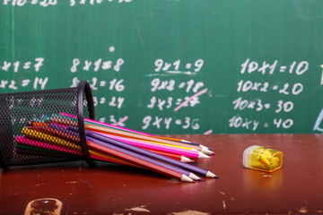 Colorful pencils of red yellow orange violet purple pink green and blue in stationary cup and steel lying on brown school desk on written with white chalk blackboard backgroung on lesson of math