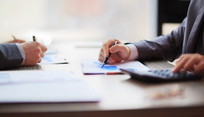 Two business people working sitting at the table. Close up of hands