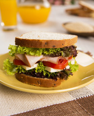 Sandwich on a white plate with turkey breast, tomato and lettuce.