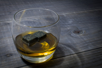 Glass of Whisky with rocks on a rustic wooden table