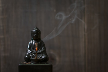 Burning Incense on Buddha Statue with Curling Smoke