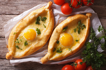 Adjarian khachapuri and vegetables close-up horizontal top view