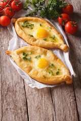 two khachapuri and fresh vegetables close-up on the table. vertical