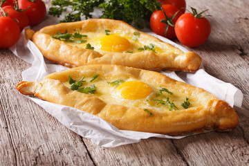 Rustic khachapuri and fresh vegetables close-up. horizontal