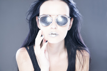 Beautiful woman fashion model portrait in sunglasses with metallic silver lips. Creative hairstyle and make up