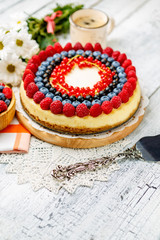 Raspberry and blueberry cheesecake on wooden table