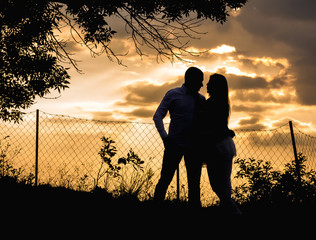 Silhouette couple enjoying in sunset. Young couple in love. Nature environment.