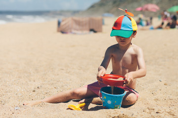 Boy sitting on beach playing with sand