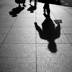 Shadows and Silhouettes of people walking on street in city