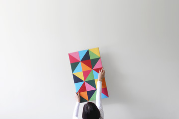 Woman decorating an empty white wall with colorful artwork