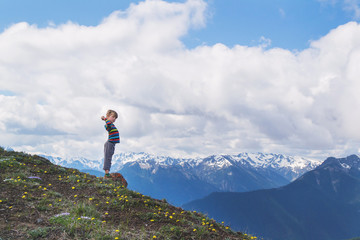 Boy standing on hill with outstretched arms