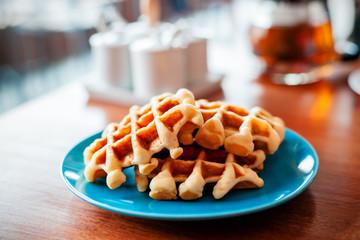 close up waffles on a blue plate