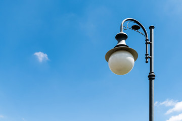 Fotomurales - Vintage Street Light Pole Against Blue Sky