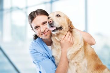Veterinarian, dog, hugging.