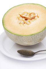 Fresh Cantaloupe Melon – A half of a fresh cantaloupe on a white plate. Spoon in foreground.