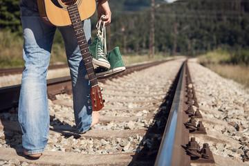 Alone traveler barefoot walk on the railway
