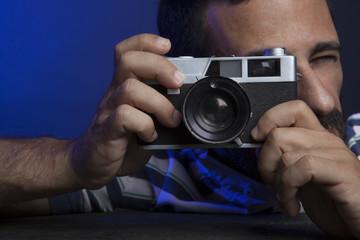 Un uomo scatta un fotografia con una vecchia macchina analogica
