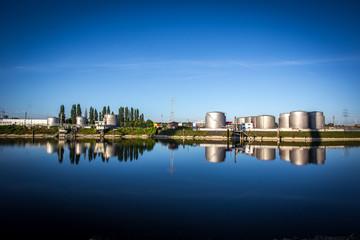 Spiegelung einer Industrieanlage im Rhein an einem Sommermorgen